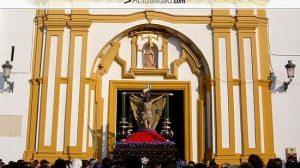El Cristo de la Vera Cruz durante la difícil salida de la Parroquia del Divino Salvador que los hermanos costaleros realizan de rodillas, y la talla roza el exorno floral / Juan C. Romero