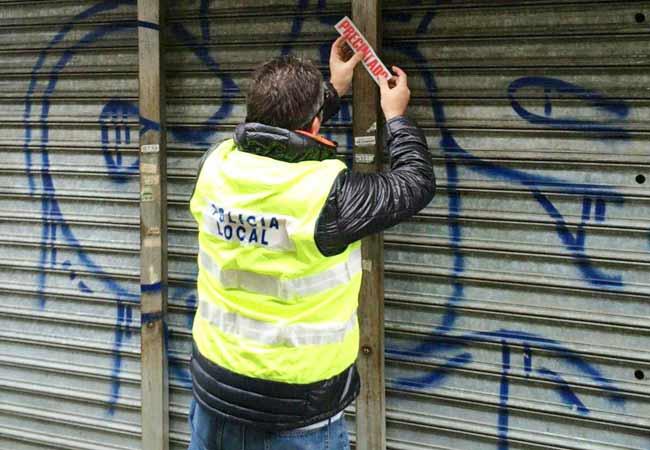 Un agente de la Policía Local procede al precinto de uno de los locales en Sevilla/ SA